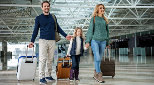 Family walking with bags at airport