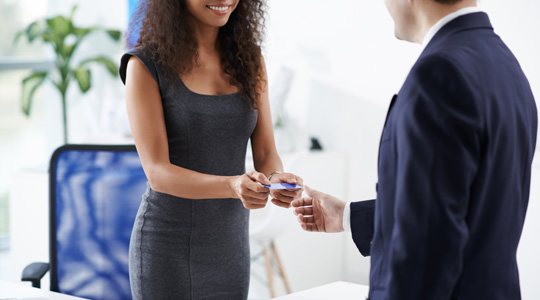 Woman employee handing card over